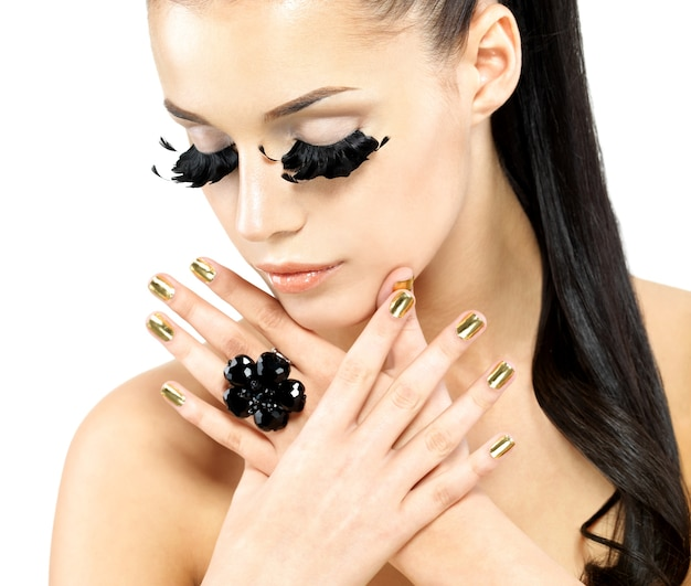 Closeup portrait of the beautiful woman with long black false eyelashes makeup and golden nails.  isolated on white background