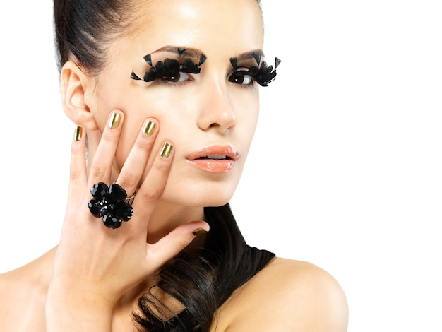 Closeup portrait of the beautiful woman with long black false eyelashes makeup and golden nails.  isolated on white wall