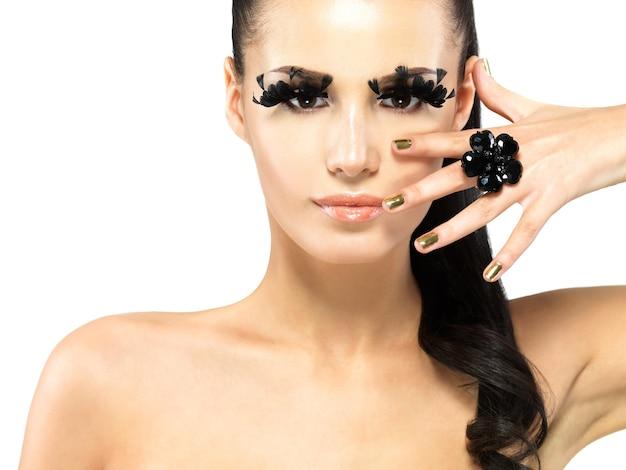 Closeup ritratto della bella donna con trucco ciglia finte nere lunghe e unghie d'oro.