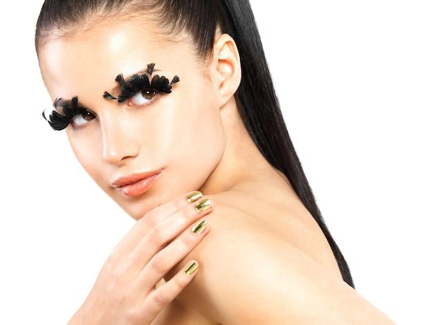 Closeup portrait of the beautiful woman with long black false eyelashes makeup and golden nails.