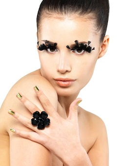 Closeup portrait of the beautiful woman with long black false eyelashes makeup and golden nails.