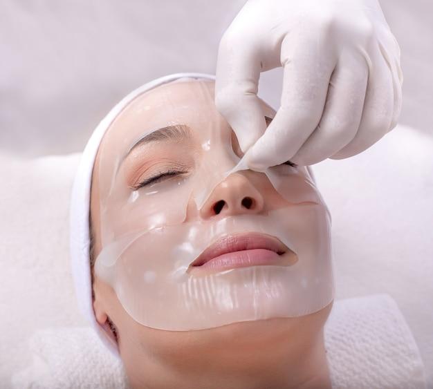 Ritratto del primo piano di una bellissima giovane donna caucasica che applica la maschera per la pelle del viso