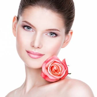 Closeup portrait of beautiful young woman with healthy skin and flower near face - isolated on white.