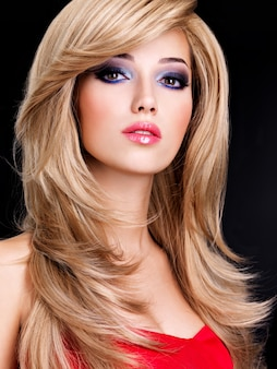 Closeup ritratto di una bellissima giovane donna con lunghi capelli bianchi e labbra rosse. modello di moda in posa nello spazio nero