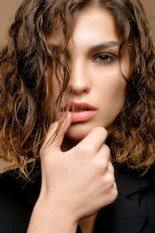 Closeup portrait of beauty fashion model with clean skin and curly hair in black jacket on beige wall, hands near lips