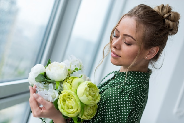 Closeup portrait of  blonde girl holding a bouquet of peonies and gently looking on it. - image