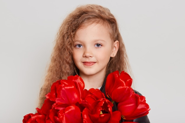 Closeup portrait of blonde girl with wavy hair looking directly at front, holding in hands large bouquet of red tulips, having calm facial expression