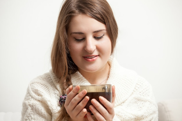 Closeup portrait of brunette woman in white sweater holding cup of tea