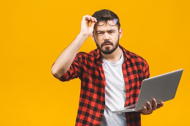 分離されたラップトップソフトウェアと混同される視力の問題を持つ眼鏡のクローズアップの肖像画ビジネス男。ビジョン関連の変更。人間の顔の表情。