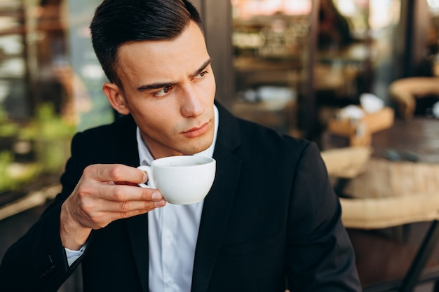 Closeup portrait of businessman  holding a cup of coffe and looking  by sideways - image
