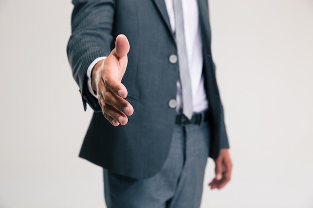 Closeup portrait of a businessman stretching hand for handshake isolated