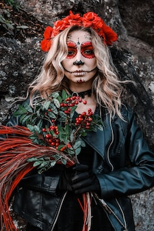 Closeup portrait of calavera catrina. young woman with sugar skull makeup and red flowers. dia de los muertos. day of the dead. halloween. santa muerte makeup woman on halloween eve. fashion creative