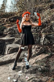 Closeup portrait of calavera catrina. young woman with sugar skull makeup throwing playing cards. dia de los muertos. day of the dead. halloween. santa muerte makeup woman on halloween eve