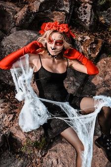 Closeup portrait of calavera catrina. young woman with sugar skull makeup and white spiderweb. dia de los muertos. day of the dead. halloween. santa muerte makeup woman on halloween eve