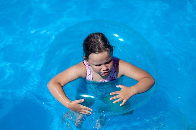 Closeup portrait of a caucasian girl holding an inflatable circle fear of swimming