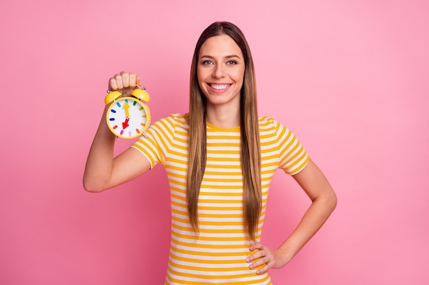 Closeup portrait of  charming cheerful girl holding in hands clock