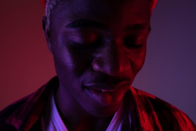 Closeup portrait of a charming handsome black man with closed eyes in neon red-blue light