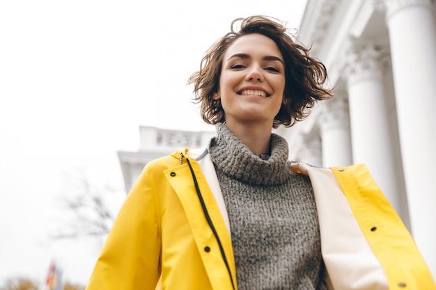 Closeup portrait of charming young woman with bob haircut enjoying walk through the city in yellow coat smiling on camera
