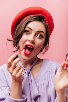 Closeup portrait of cheerful green-eyed girl painting lips with red lipstick on isolated background.