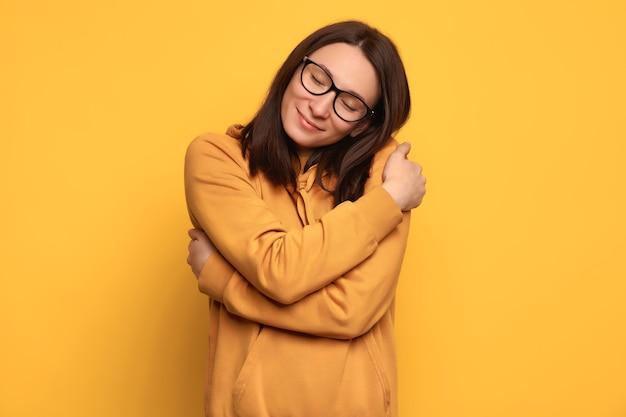 クローズアップの肖像画自信を持って笑顔の女性のメガネとオレンジ色の居心地の良いジャンパーを保持し、黄色の背景で隔離の自分を抱き締めます。