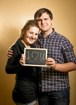 Closeup portrait of couple in love holding blackboard with