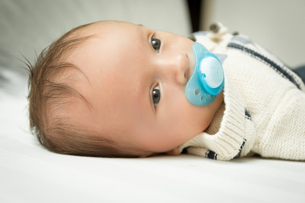 Closeup portrait of cute 1 months old baby boy with soother lying on bed
