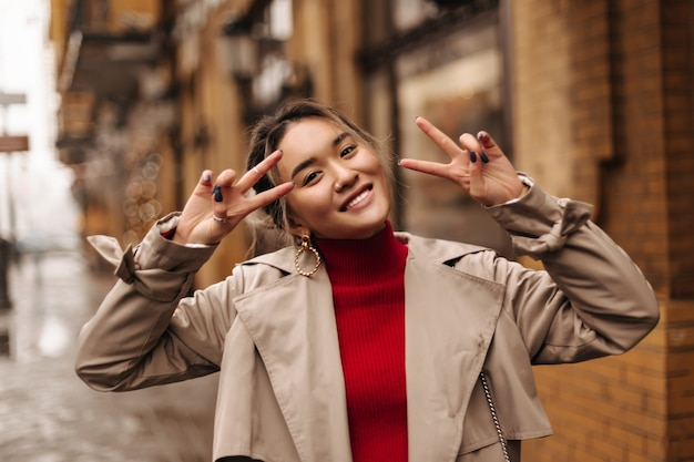 Closeup portrait of cute asian woman in red top and beige trench coat smiling and showing peace signs on wall of beautiful building