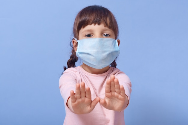 Closeup portrait of cute child wearing casual shirt and medical mask, female kid showing stop gesture with both palms