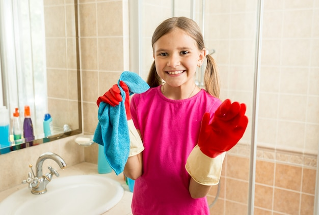 Closeup portrait of cute girl in rubber gloves doing cleanup at bathroom