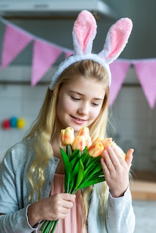 Closeup portrait of cute little girl wearing bunny ears and holding a bouquet of tulips