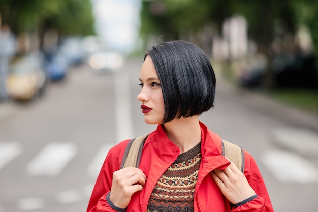 Closeup portrait of cute pensive girl in red jacket and backpack on the street