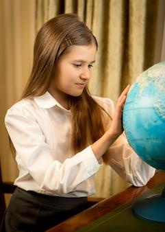 Closeup portrait of cute schoolgirl looking at earth globe