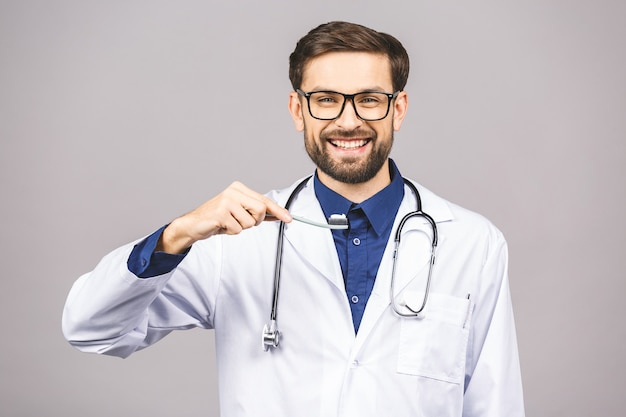 Closeup portrait of a dentist holding a toothbrush, isolated