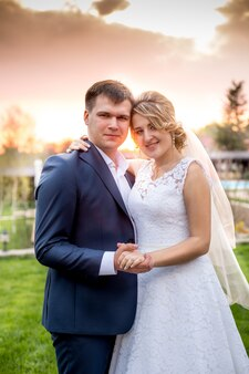 Closeup portrait of elegant newlyweds hugging at park at sunset