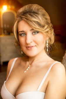 Closeup portrait of elegant woman with green eyes in bra posing at hotel room