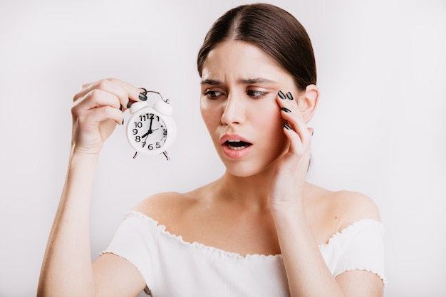 Closeup portrait of excited european woman on isolated wall. girl sadly looks at white clock.