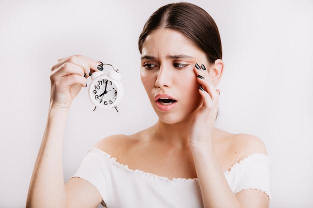Ritratto del primo piano della donna europea eccitata sulla parete isolata. la ragazza guarda tristemente l'orologio bianco.