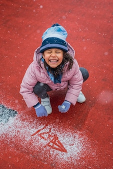 Closeup portrait of an excited girl playing with fresh snow during a snowfall in the wintertime