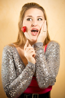 Closeup portrait of excited woman holding decorative heart on stick