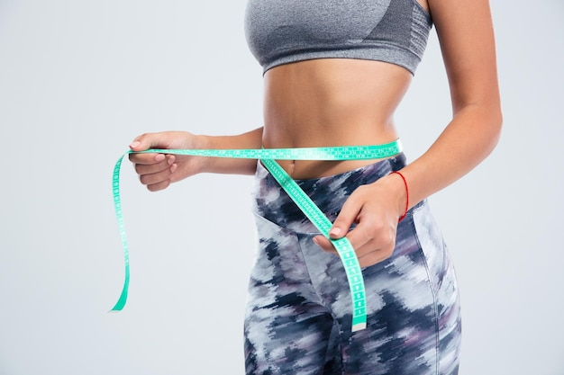 Closeup portrait of a female sports body with measuring tape isolated on a white wall