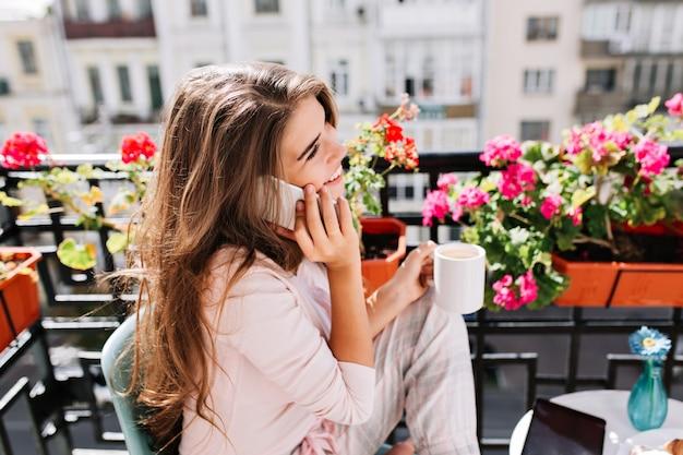 Ritratto del primo piano dalla ragazza graziosa laterale in pigiama facendo colazione sul balcone la mattina soleggiata. ha conseguito una tazza, parlando al telefono sorridendo.