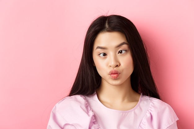 Closeup portrait of funny asian woman squinting eyes and making silly faces standing against pink ba...