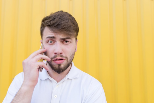 Closeup portrait of a funny man talking on the phone on a yellow wall.