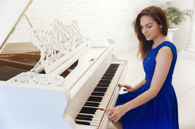 Closeup portrait of a girl in blue dress sitting at the piano and play the piano
