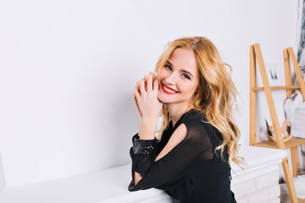 Closeup portrait of girl with blonde wavy hair in modern luxury room. young woman smiling. wearing stylish elegant black dress with paillettes on sleeves.