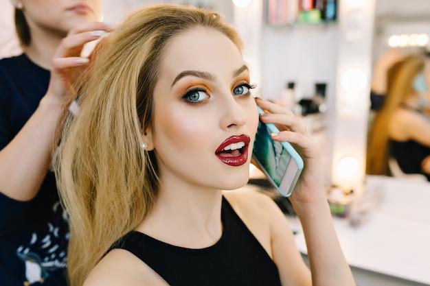 Closeup portrait gorgeous blonde model preparing to celebration, party in hairdresser salon