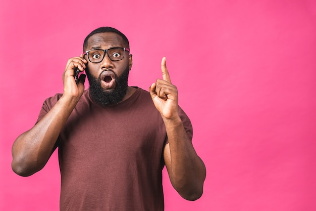 Closeup portrait of handsome african american black man, shocked, surprised, wide open mouth, using mobile phone, isolated on pink background. negative human emotions.