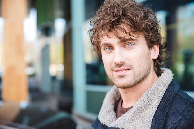 Closeup portrait of handsome attractive happy content curly male in the city