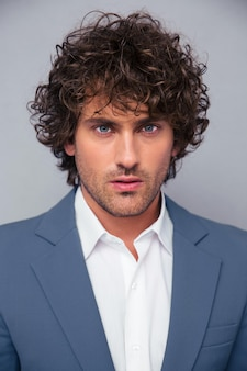 Closeup portrait of a handsome businessman with curly hair on gray wall