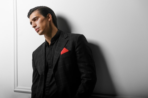 Closeup portrait of handsome man in black suit with red silk scarf in pocket, over white background.